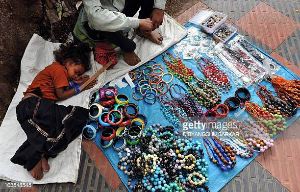 An Indian child sleeps next to a young street vendor selling bangles and necklaces to tourists at a sidewalk in Bangalore on August 23 2010 AFP...