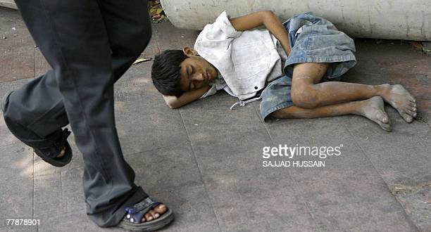 An Indian child sleeps on the roadside in Mumbai 13 November 2007 Street children like these often have a tough childhood in India's financial...