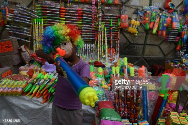 An Indian child the son of a street vendor poses at a stall selling water guns for the upcoming Hindu festival of Holi in Siliguri on March 13 2014...