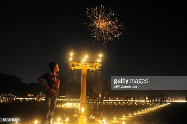 TOPSHOT An Indian child watches fireworks at the Madan Mohan Malviya stadium during Diwali Festival in Allahabad on October 18 2017 Diwali the Hindu...