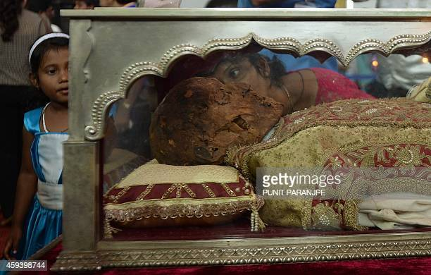 An Indian Christian is watched by a child as she kisses a casket carrying the remains of the St Francis Xavier at the Se Cathedral in Goa on November...