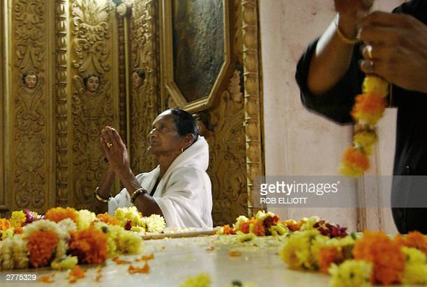 An Indian Christian worshipper raises her hands in prayer as another prepares a floral garland at the base of Saint Francis Xavier's raised pediment...