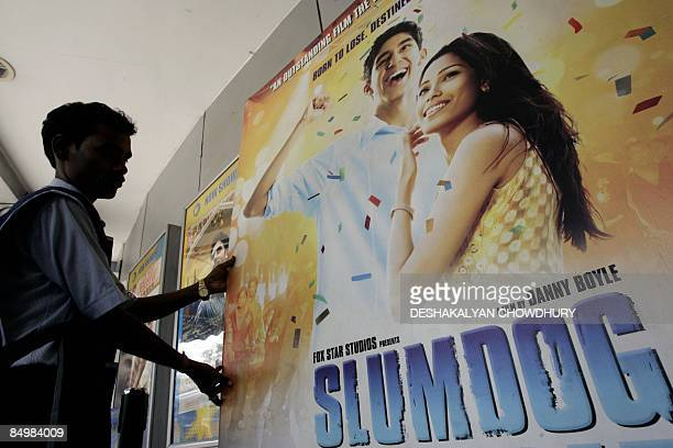 An Indian cinema workers positions a poster for the movie 'Slumdog Millionaire' in Kolkata on February 23 2009 India basked in the reflected glory of...