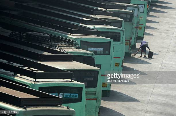 An Indian civic worker cleans up next to buses parked at a depot during a transport strike in Chennai on January 5 2018 The Tamil Nadu State...