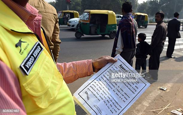 An Indian civil defence personnel holds a pamphlet detailing a scheme to cut smog at a traffic intersection in New Delhi on January 1 2016 More than...