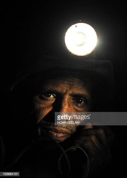 An Indian coal miner uses the telephone inside an underground tunnel of a mine owned by the Sinagareni Collieries Company Limited at Godavarikhani...