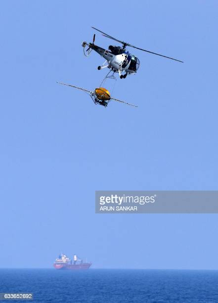 An Indian Coast Guard helicopter transports an Oil Spill Disperser from the coastguard ship 'Varad' during a scout for oil spills over the waters of...