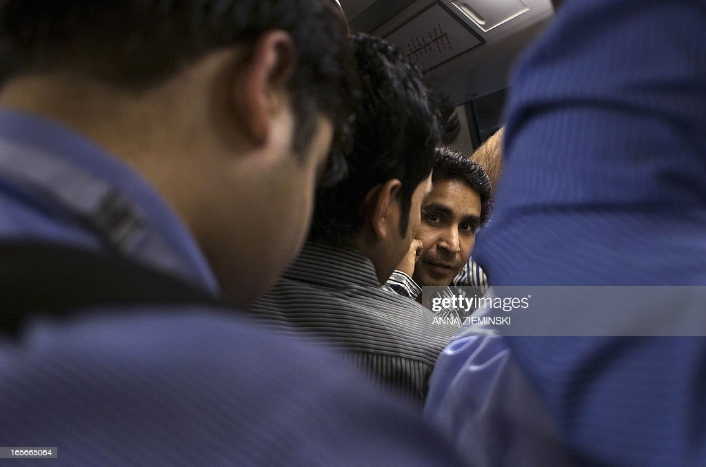 An Indian commuter listens on his mobile phone while travelling on the Metro in New Delhi on April 5, 2013. Having celebrated 10 years of service in December 2012, over two million passengers travel by Delhi Metro daily with 2500 train trips made each day. AFP PHOTO/ Anna ZIEMINSKI
