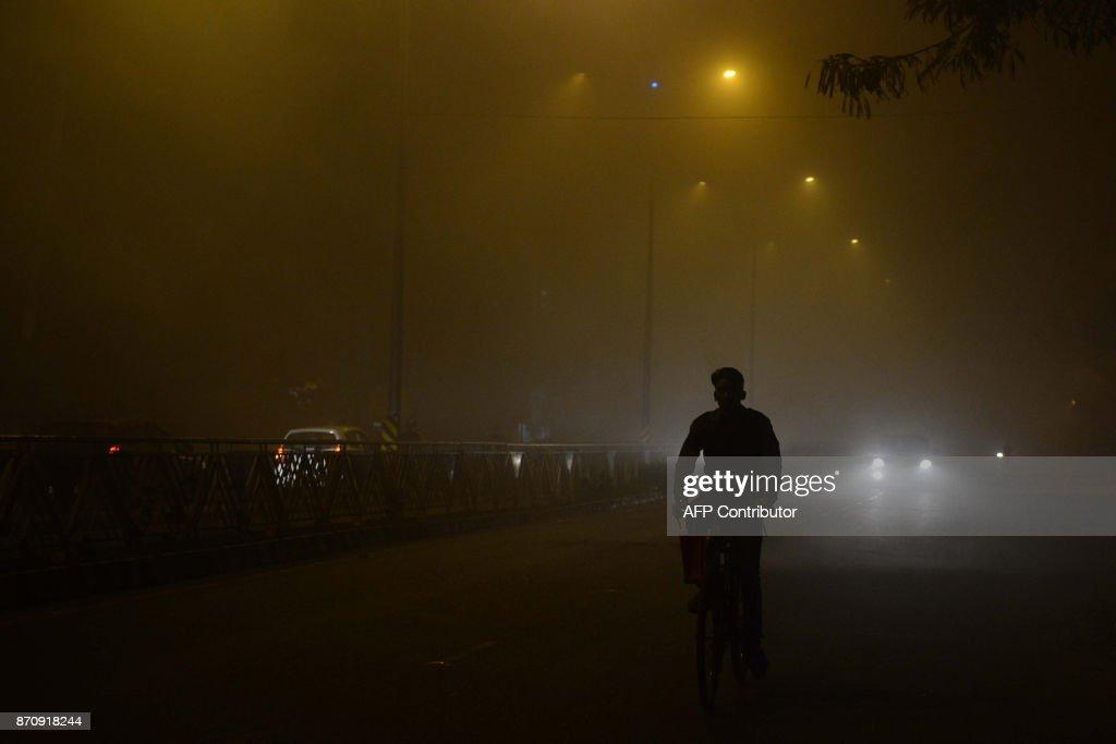 An Indian commuter makes his way through thick fog in Amritsar on November 6 2017 / AFP PHOTO / NARINDER NANU