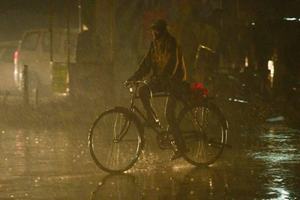 An Indian commuter rides a bike under the rain in Jalandhar on December 11 2017 / AFP PHOTO / Shammi MEHRA