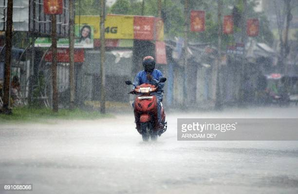 An Indian commuter rides a scooter through heavy rain brought by Cyclone Mora in Agartala the capital of northeastern state of Tripura on June 1 2017...