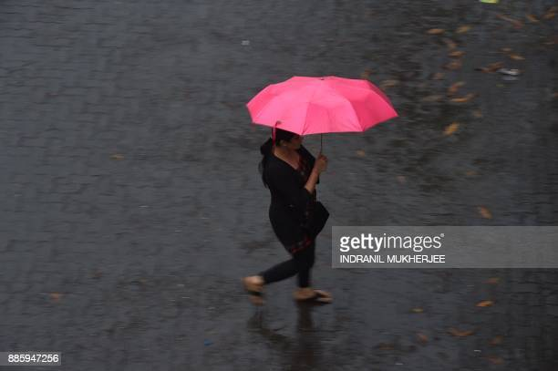 An Indian commuter rushes across a street during rain from Cyclone Ochki in Mumbai on December 5 2017 Cyclone Ockhi brought heavy rain to Mumbai as...