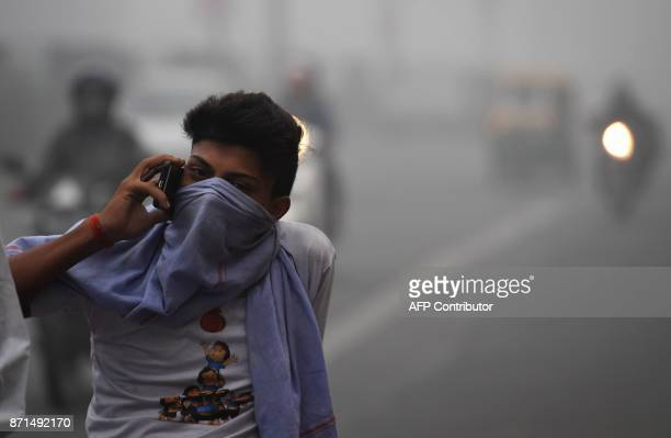 An Indian commuter talks on a phone amid heavy smog in New Delhi on November 8 2017 Delhi shut all primary schools on November 8 as pollution levels...