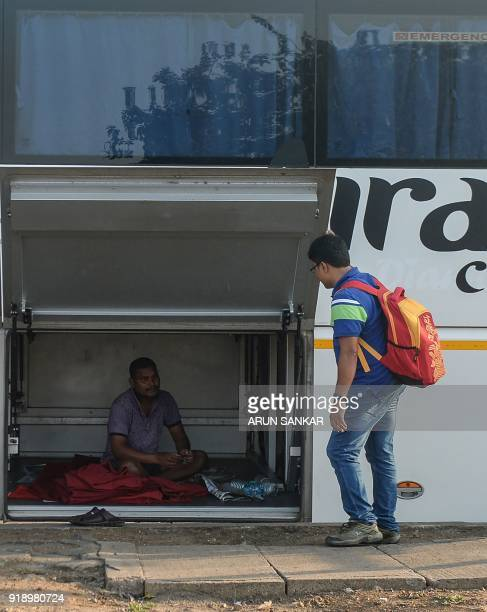 An Indian commuter talks to a state transportation employee rest inside a bus luggage compartment at a bus terminal in Chennai on February 16 2018...