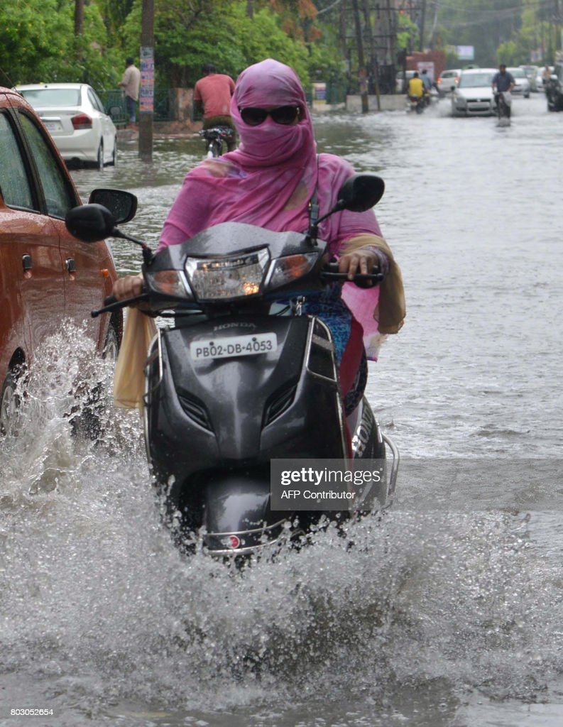 An Indian commuters makes her way along a flooded street after heavy rain in Amritsar on June 29 2017 / AFP PHOTO / NARINDER NANU
