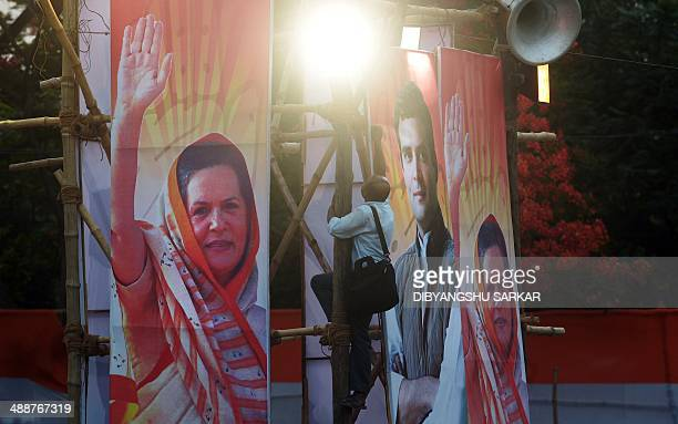 An Indian Congress Party supporter removes a poster bearing the image of party Vice President Rahul Gandhi and President Sonia Gandhi after Rahul...