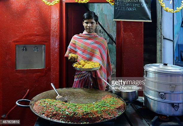 An Indian cook poses for a photograph as he prepares to make 'samosa' at a chaat or savory snack stall on Food Street in Bangalore on October 24 2014...