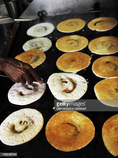 An Indian cook prepares 'dosas' on a tawa traditional Indian pan in the kitchen of M Putturaju's restaurant in Bangalore on August 5 2010 Fortytwo...