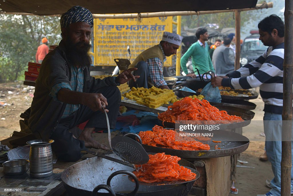 An Indian cook prepares jalebi sweets for sale at a roadside stall on the outskirts of Amritsar on December 29 2016 / AFP / NARINDER NANU