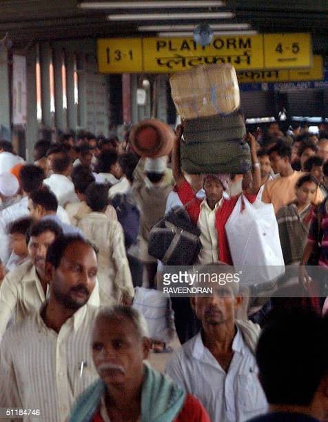 An Indian coolie carries luggage on his head as commuters crowd an overbridge at New Delhi railway station, 18 August 2004. India is expected to...