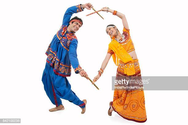 An Indian couple in traditional wear performing Dandiya Raas over white background