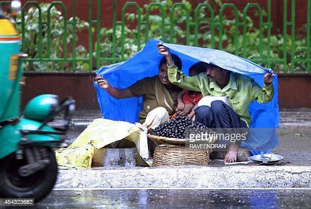 An Indian couple shield themselves under a plastic sheet as they wait for customers to buy Jamun during a heavy downpour in New Delhi 28 June 2007 A...