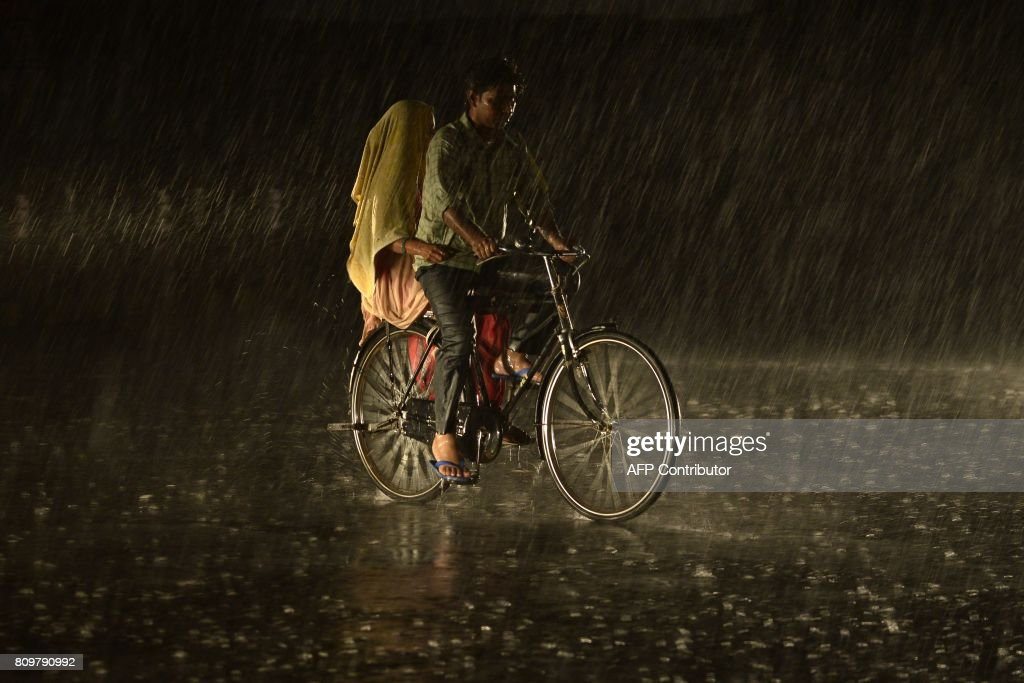 An Indian couple travels ride a bike as heavy rain falls in Jalandhar on July 6 2017 / AFP PHOTO / SHAMMI MEHRA