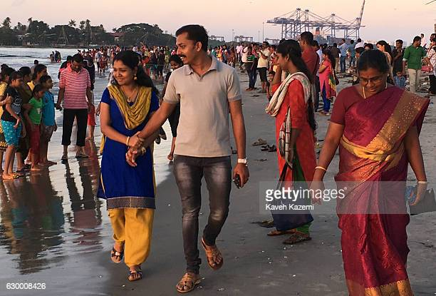 An Indian couple walk on the beach at sunset where many others also present for enjoying themselves on October 10 2016 in Kochi India Kochi is a city...