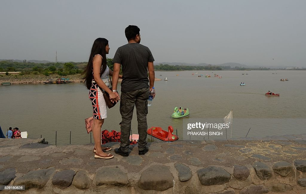 An Indian couple watch as visitors enjoy boating on Sukhna Lake in Chandigarh on May 8 2016 / AFP / PRAKASH SINGH
