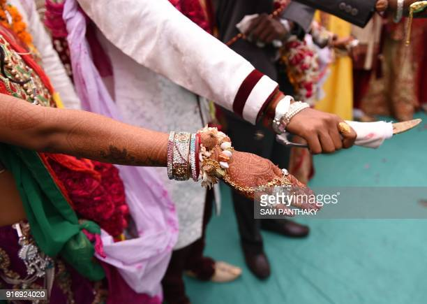 An Indian couples take part in a mass wedding for members of the Adivasi Bhil tribal community in Ahmedabad on February 11 2018 Some 35 couples were...