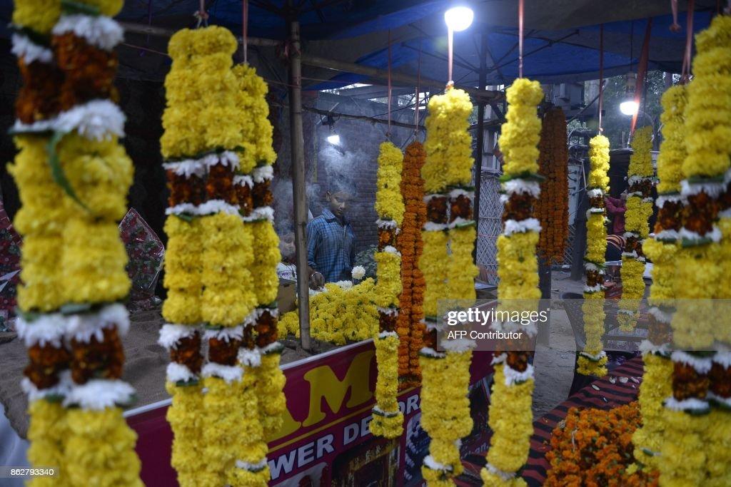 An Indian craftsman assembles flower garlands ahead of the Diwali Festival at flower market in Jalandhar on October 18 2017 Diwali the Hindu festival.