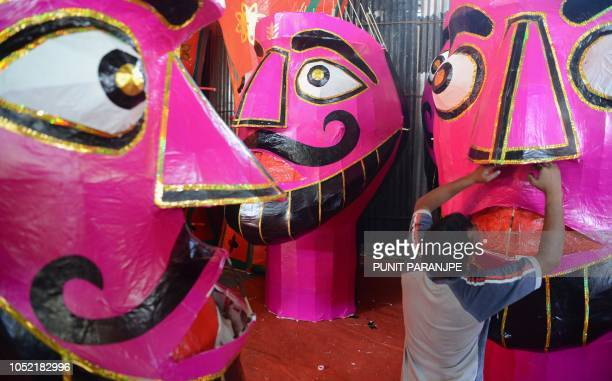 An Indian craftsman gives final touches to a paper effigy of the Hindu demon king 'Ravana' ahead of the Hindu festival of Dussehra in Mumbai on...