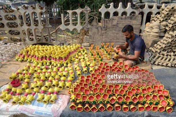 An Indian craftsman paints earthen lamps ahead of the Hindu festival of Diwali in Amritsar on October 29 2018 The decorated lamps are in heavy demand...