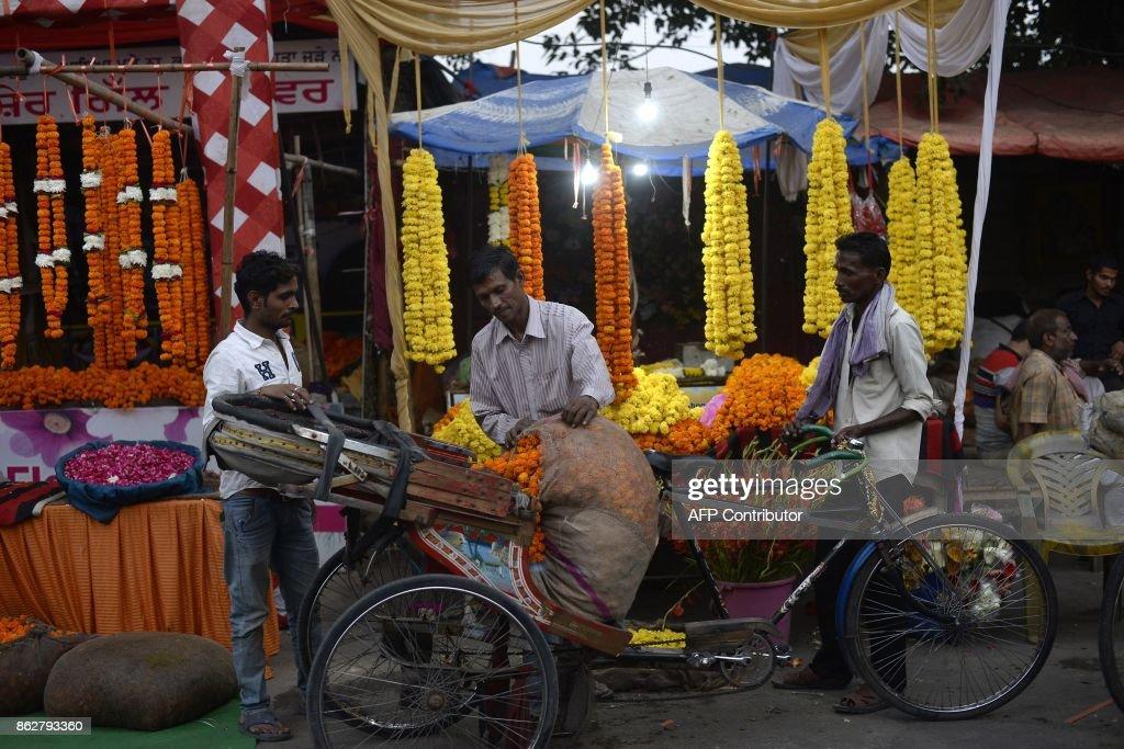 An Indian craftsman unloads flowers stacks for make garlands ahead of the Diwali Festival at flower market in Jalandhar on October 18 2017 Diwali the.