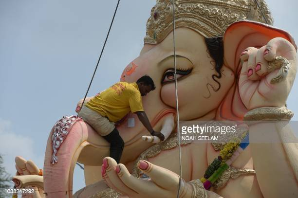 An Indian crane worker climbs an idol of Hindu deity Ganesh to secure it before immersing it in the Hussain Sagar Lake on the eleventh day of the...