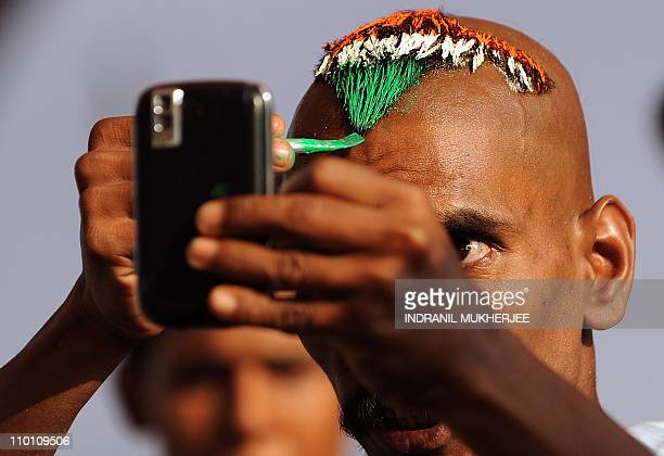 An Indian cricket fan Sudhir Kumar Gautam applies the Indian national flag colours to his hair during a training session of the Indian team ahead of...