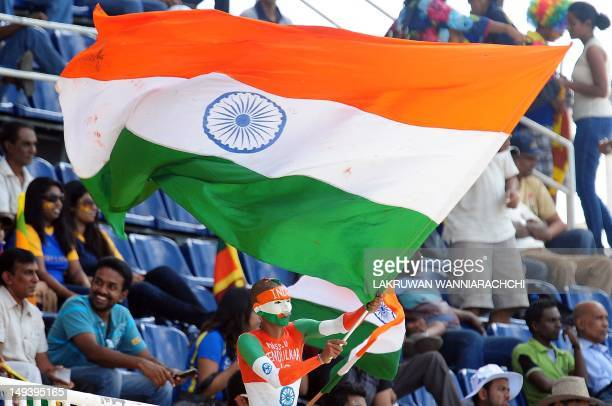 An Indian cricket fan waves the Indian national flag during the third one day international match between Sri Lanka and India at the RPremadasa...