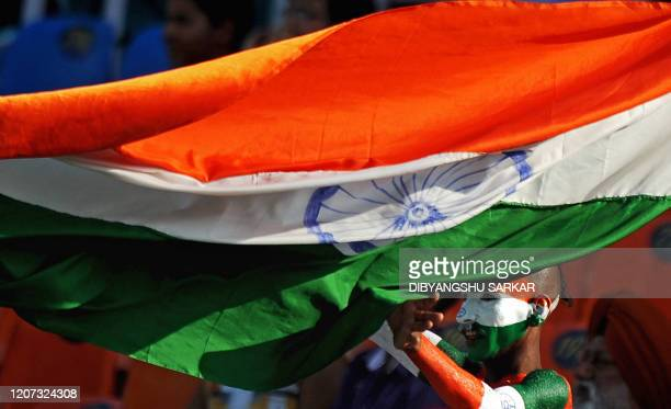 An Indian cricket fan with his body painted in the country's colours waves India's national flag to support his team during the third day of the...