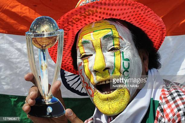 An Indian cricket fan with his face painted holds a replica Cricket World Cup trophy as he cheers for the Indian cricket team during The ICC Cricket...