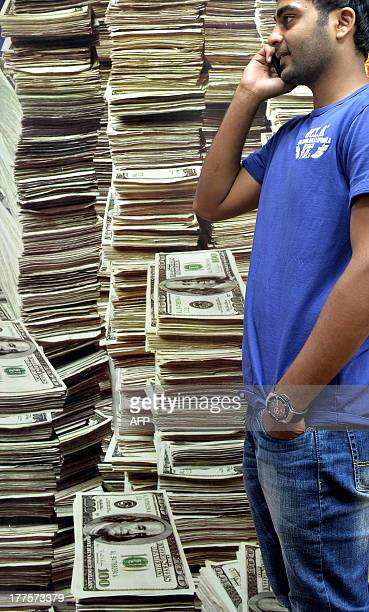 An Indian customer at a foreign exchange outlet speaks on a phone in front a poster of US dollars in Bangalore on August 24 2013 The rupee staged a...