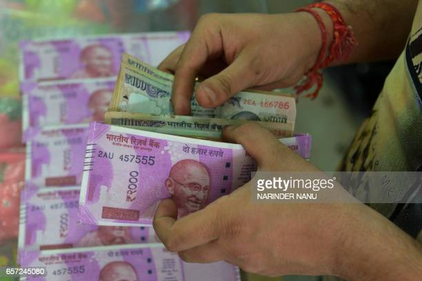 An Indian customer buys a wallet decorated with an image of the new Indian Rupee 2000 note at a gift shop in Amritsar on March 24 2017 / AFP PHOTO /...