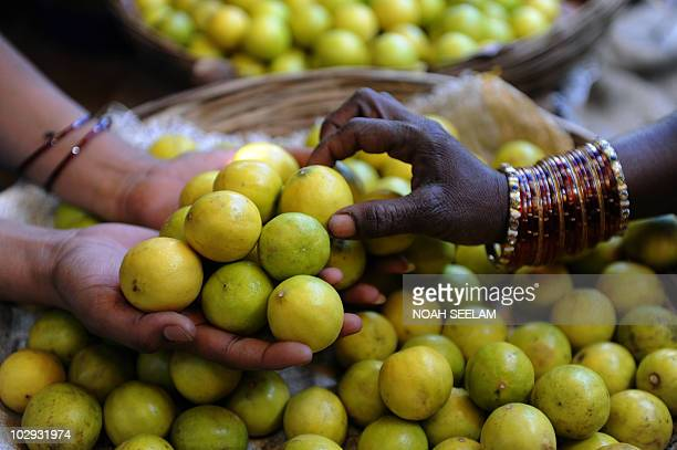 An Indian customer buys limes from a vendor at a wholesale market on the outskirts of Hyderabad on April 17 2009 Prices of food items such as pulses...