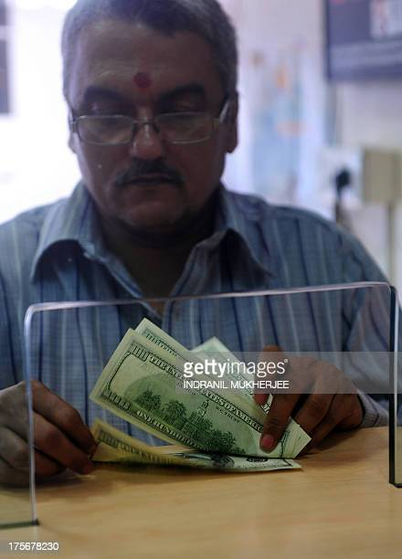 An Indian customer counts US Dollars at a foreign exchange dealer in Mumbai on August 6 2013 India's rupee plunged to a fresh record low against the...