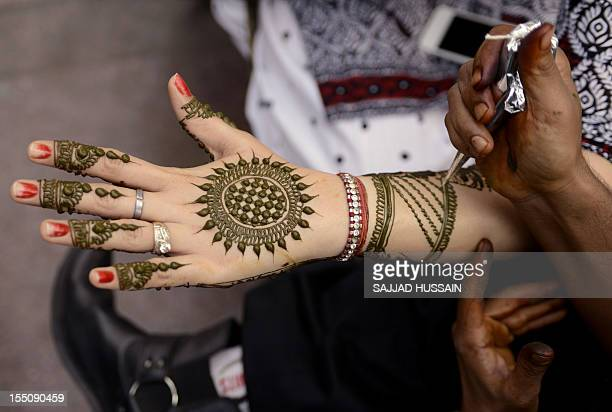 An Indian customer has her hand decorated with henna on the eve of the Karva Chauth the Husband's Day festival in New Delhi on November 1 2012 Karva...