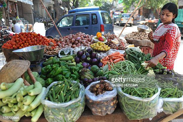 An Indian customer purchases vegtables from a roadside stall in New Delhi on September 20, 2011. India's benchmark wholesale price index -- the...