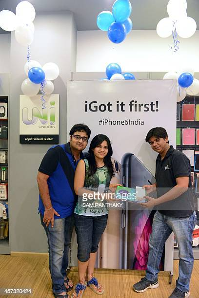 An Indian customer receives her new Apple iPhone 6 at the Unicorn Infosolutions Apple Premium Reseller store in Ahmedabad early on October 17 2014...