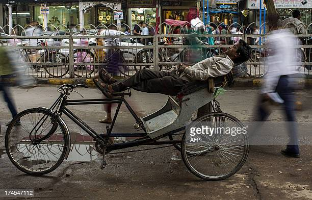 An Indian cycle rickshaw driver sleeps as pedestrians walk past on a street in New Delhi on July 27 2013 India is facing a host of economic problems...