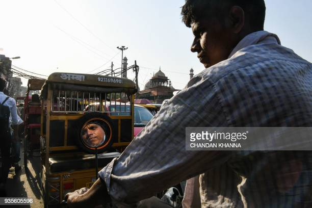 TOPSHOT An Indian cycle rickshaw puller rides through a lane in the old quarters of New Delhi on March 21 2018 / AFP PHOTO / CHANDAN KHANNA