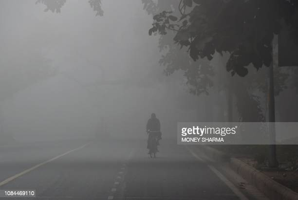 TOPSHOT An Indian cyclist cycles amid heavy smog and fog conditions in New Delhi on January 18 2019