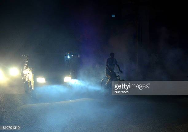 An indian cyclist passes through smoke from fumigation in a busy old street of Allahabad on September 27201621 people died of dengue in last 3 weeks...